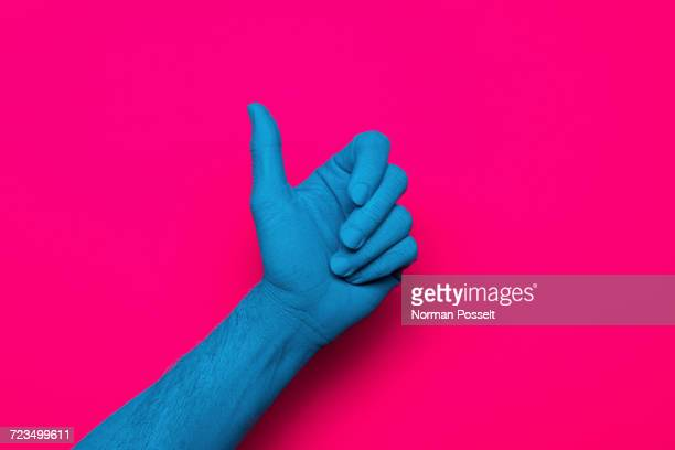 Close-up of blue painted hand gesturing thumb up against pink background