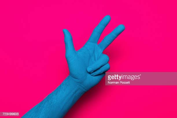 Close-up of blue painted hand showing peace sign against pink background