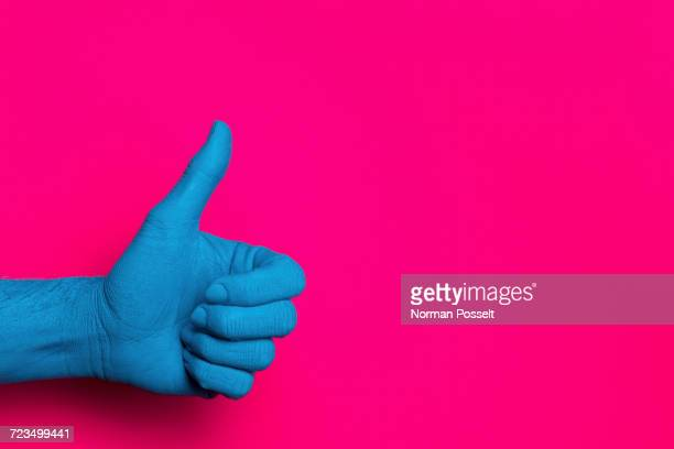 Close-up of blue painted hand showing thumb up against pink background