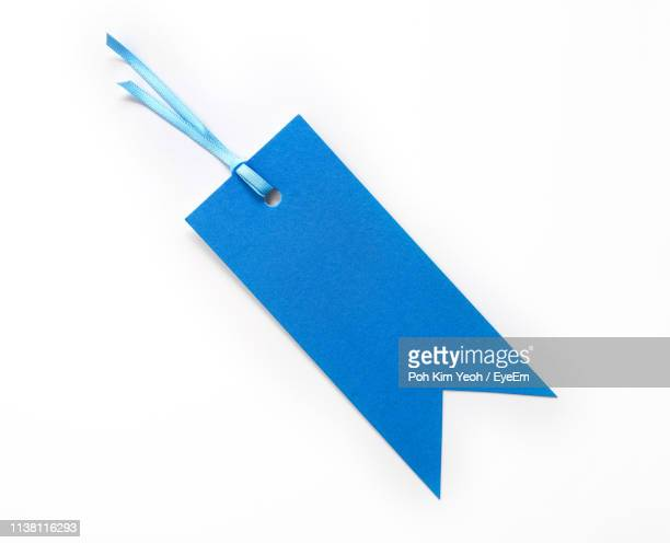 close-up of blue paper on white background - price tag stock pictures, royalty-free photos & images