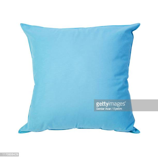 close-up of blue pillow against white background - pillow stock pictures, royalty-free photos & images