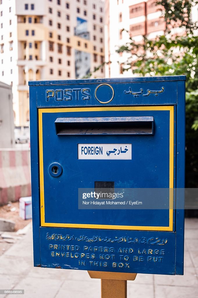 Close-Up Of Blue Public Mailbox On Footpath : Stock Photo