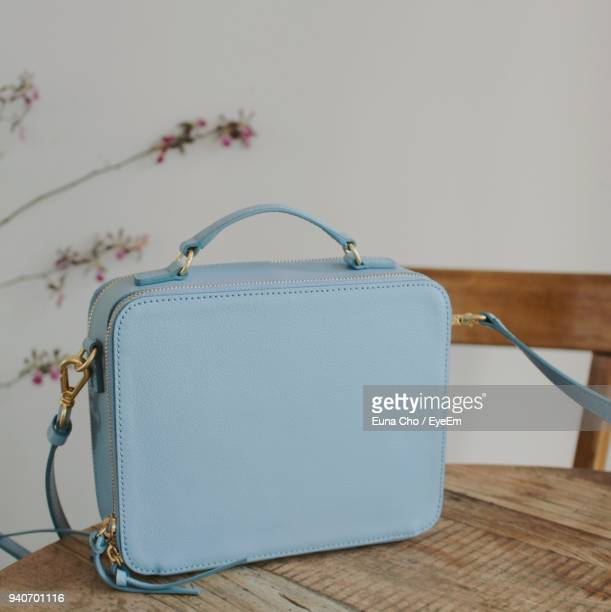 Close-Up Of Blue Purse On Wooden Table