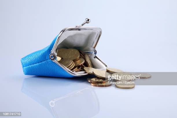 Close-Up Of Blue Purse With Coins Against White Background