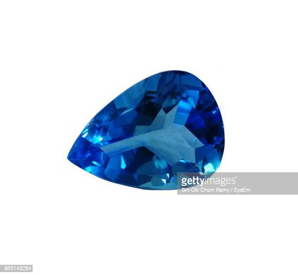 close-up of blue sapphire over white background - saffier stockfoto's en -beelden
