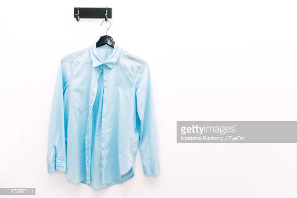 close-up of blue shirt hanging from hook over white background - 収納ラック ストックフォトと画像