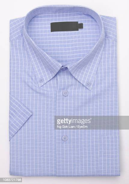 close-up of blue shirt over white background - shirt stock pictures, royalty-free photos & images