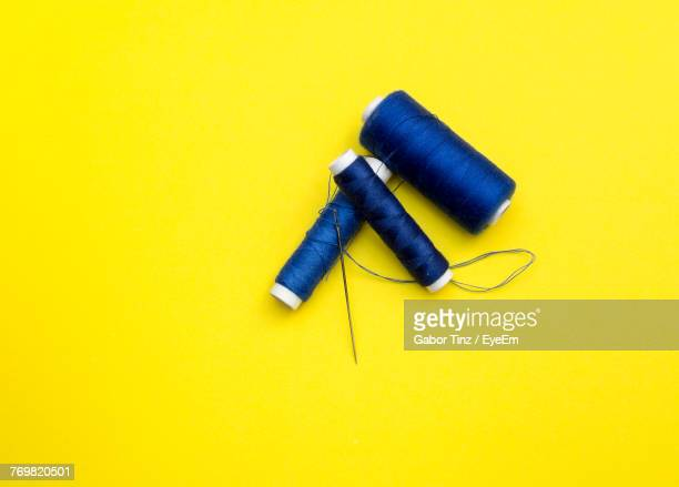 close-up of blue spools with needle over yellow background - thread stock pictures, royalty-free photos & images