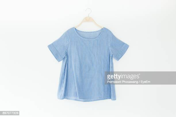 close-up of blue top hanging against white background - top garment stock pictures, royalty-free photos & images