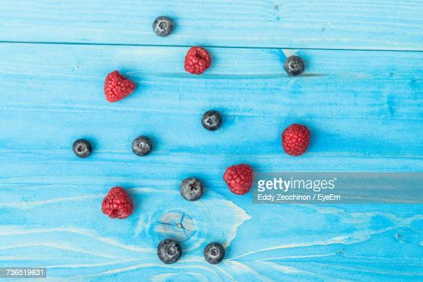 Close-Up Of Blueberries And Raspberries On Blue Wooden Table