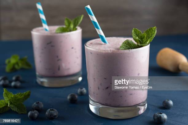 close-up of blueberry smoothie in glass on table - milkshake stock photos and pictures