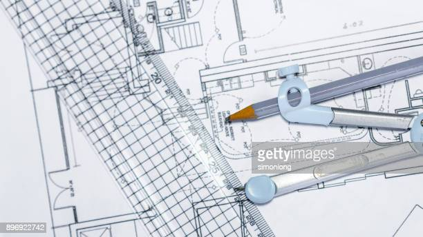 Close-Up Of Blueprint With Ruler And drawing compass On Table