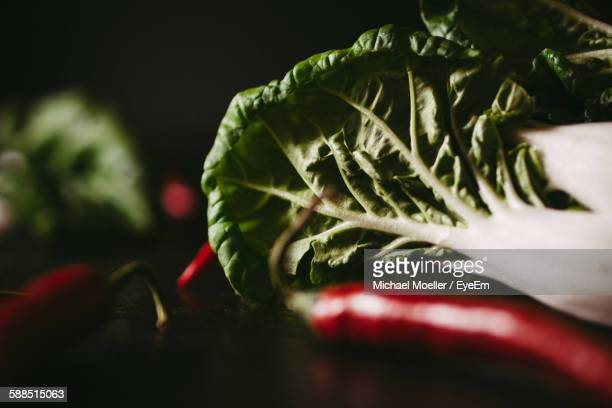 Close-Up Of Bok Choy And Red Chili Pepper On Black Background