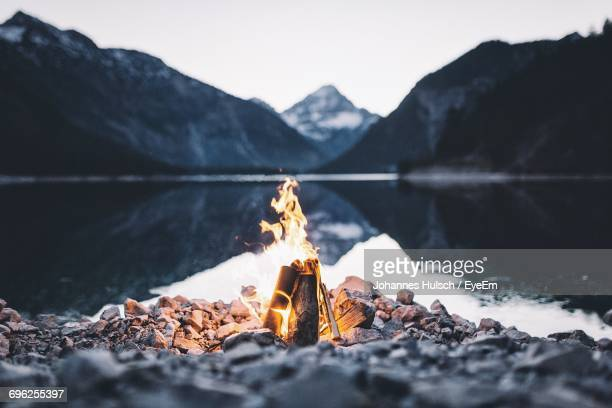 close-up of bonfire against mountain - campfire stock pictures, royalty-free photos & images