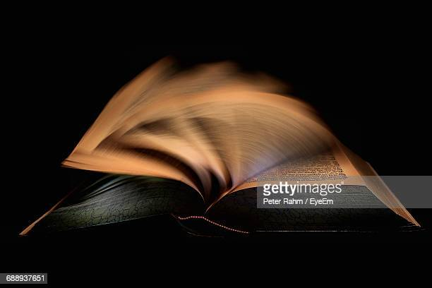 Close-Up Of Book Against Black Background