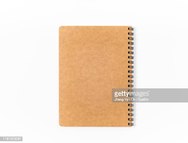 close-up of book against white background - spiral notebook stock pictures, royalty-free photos & images