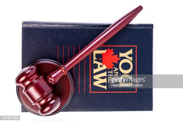 Close-Up Of Book And Gavel Over White Background