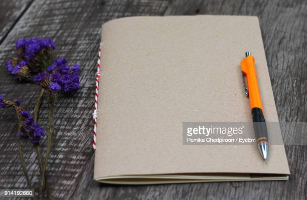 Close-Up Of Book And Pen By Flowers On Table