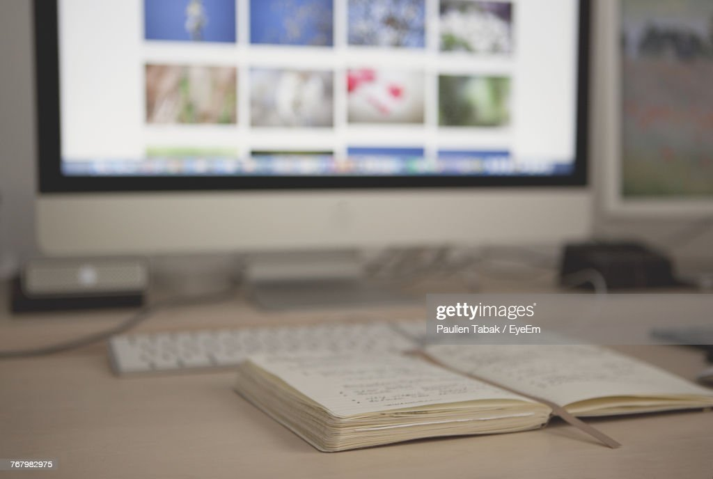 Close-Up Of Book By Desktop Computer On Table : Stockfoto