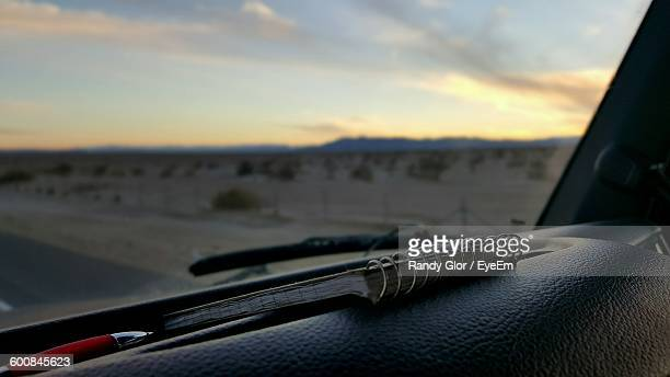 Close-Up Of Book On Car Against Field And Sky During Sunset