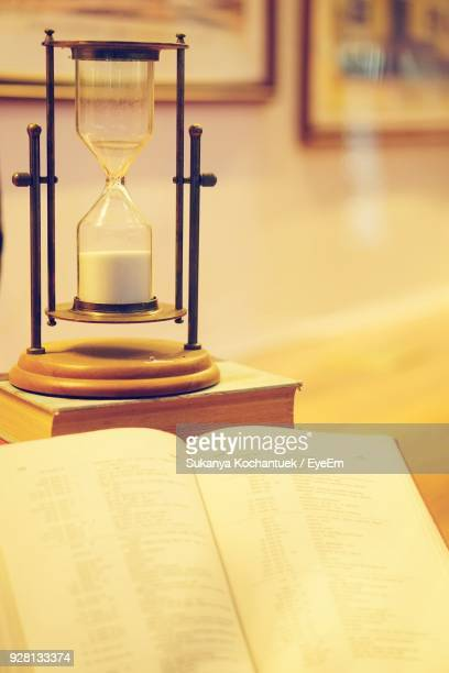 Close-Up Of Book With Hourglass On Table