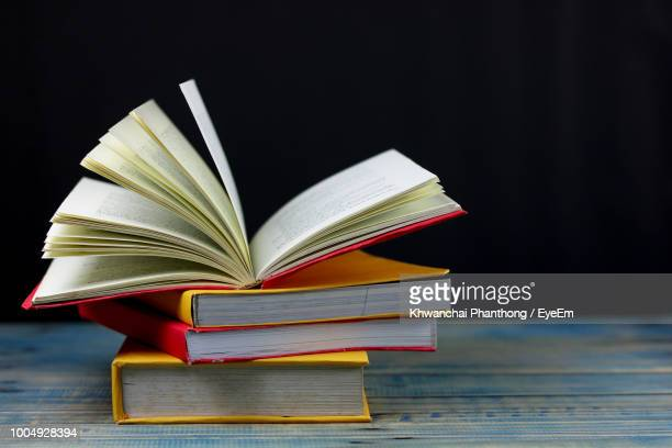 Close-Up Of Books On Table Against Black Background