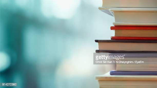 Close-Up Of Books Stacked Over Table
