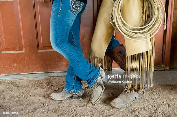 Closeup of boots of cowgirl and cowboy in front of barn door at Averill's Flathead Lake Lodge a dude ranch near Kalispell Montana United States