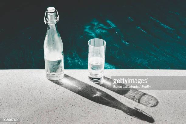 close-up of bottle and glass on retaining wall by lake - bottle water stock photos and pictures