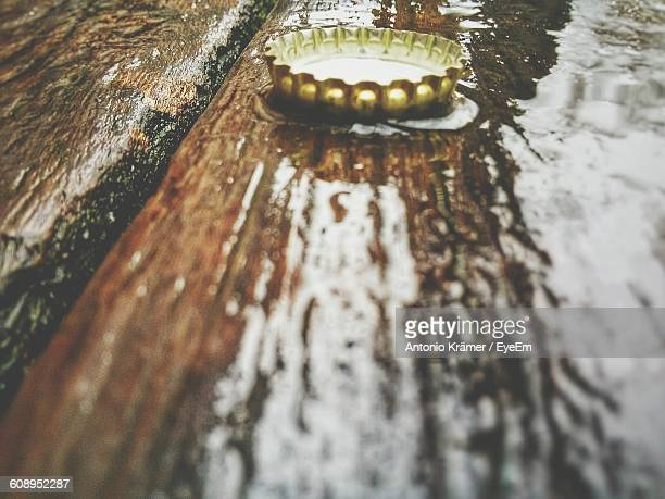 Close-Up Of Bottle Cap On Bench During Winter