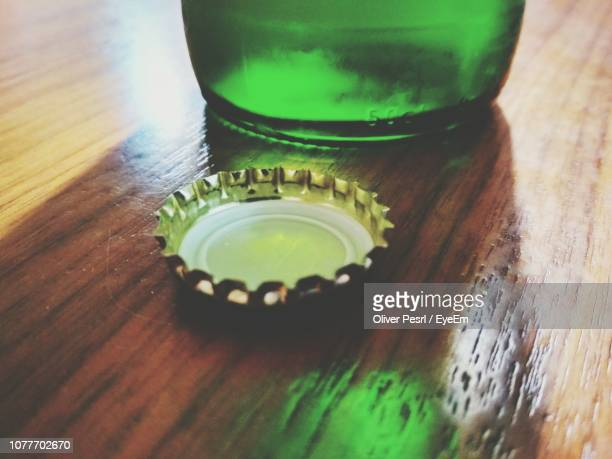 close-up of bottle cap on wooden table - beer bottle stock pictures, royalty-free photos & images