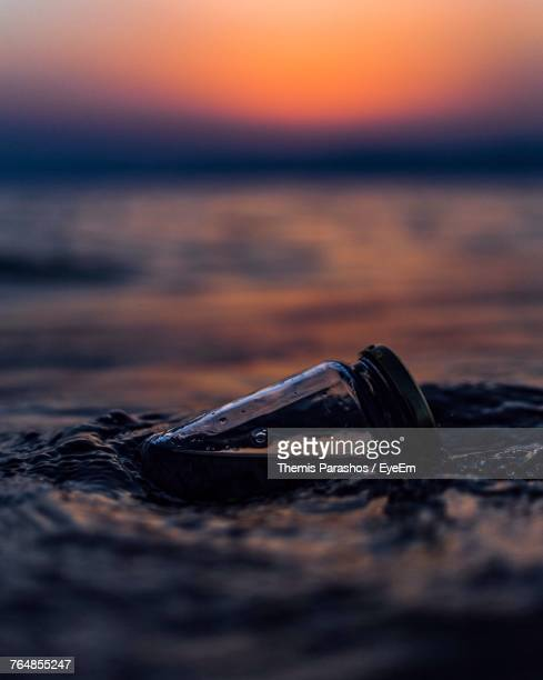 Close-Up Of Bottle In Sea During Sunset