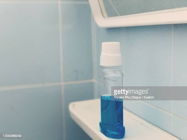 close-up of bottle on tile in bathroom - mouthwash stock pictures, royalty-free photos & images