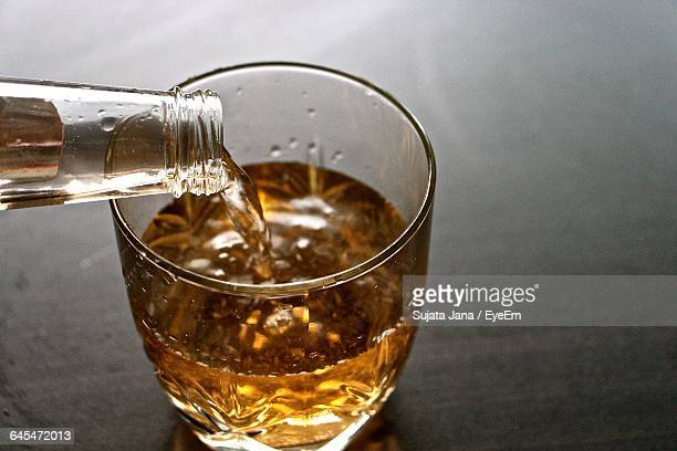 Close-Up Of Bottle Pouring Beer In Glass On Table