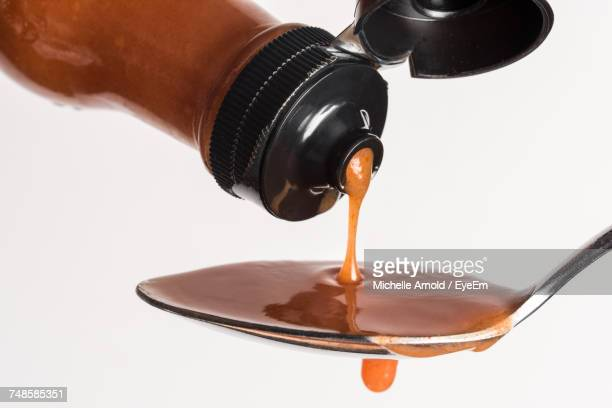 Close-Up Of Bottle Pouring Hot Sauce In Spoon Against White Background