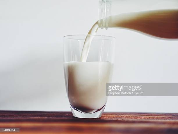 Close-Up Of Bottle Pouring Milk In Glass On Table