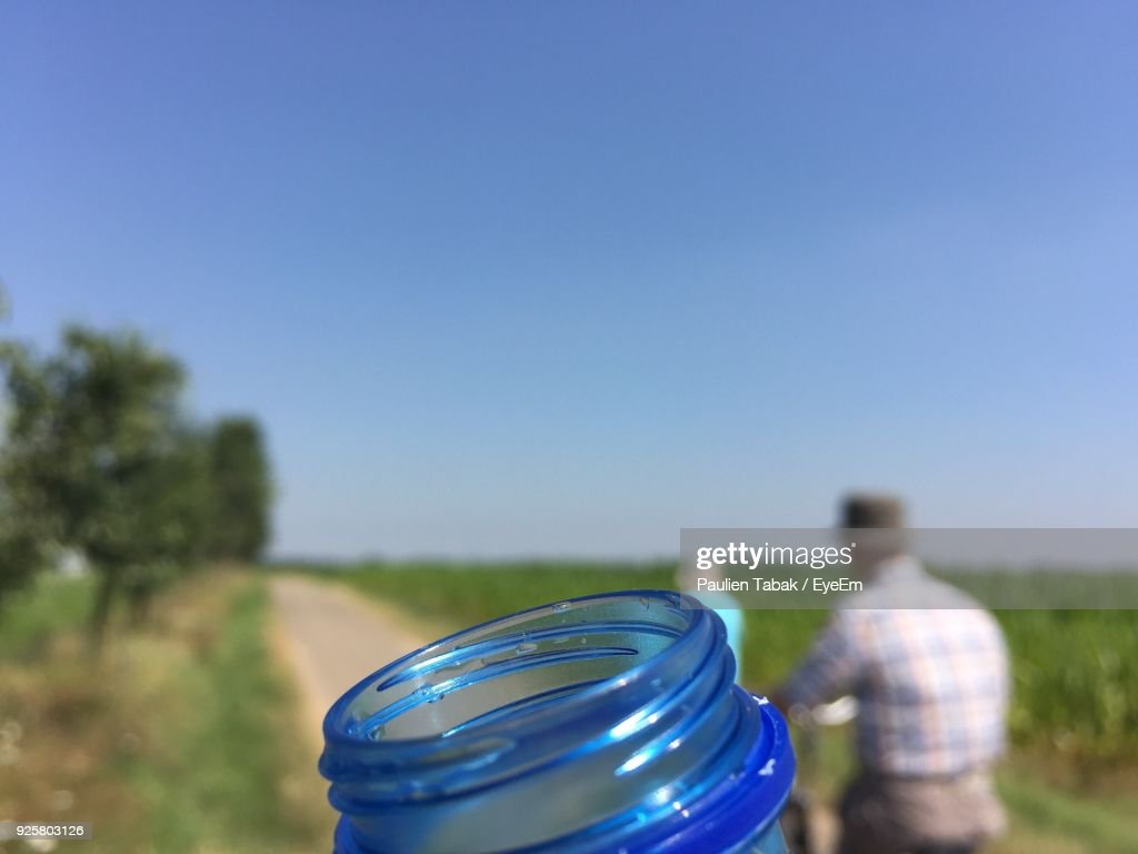 Close-Up Of Bottle With Men On Field Against Sky : Stockfoto