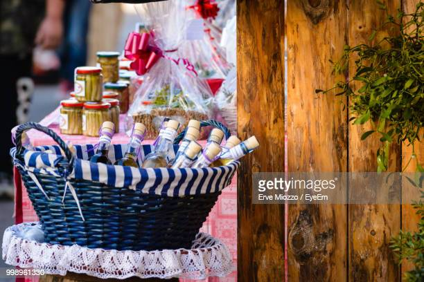 Close-Up Of Bottles In Wicker Basket For Sale At Market Stall