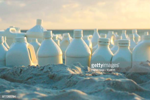 Close-Up Of Bottles On Sand At Beach During Sunset
