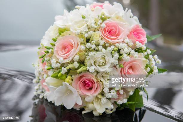 Close-Up Of Bouquet On Car Hood During Wedding Ceremony