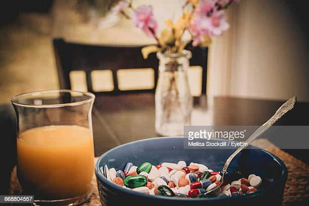 Close-Up Of Bowl Full Of Pills With Glass Of Juice