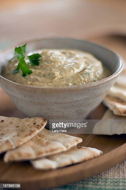 Close-up of bowl of hummus with pita bread around it