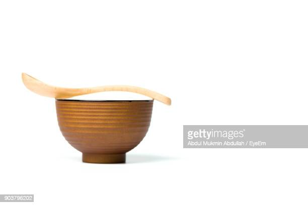 Close-Up Of Bowl With Wooden Spoon Over White Background