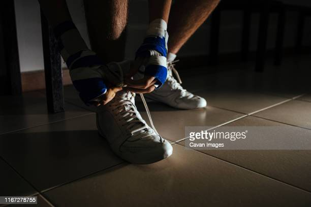 closeup of boxer feet  tying shoes before training in gym. - locker room stock pictures, royalty-free photos & images
