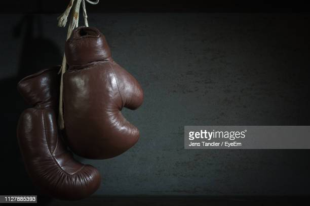 close-up of boxing gloves hanging against wall - boxing gloves stock pictures, royalty-free photos & images
