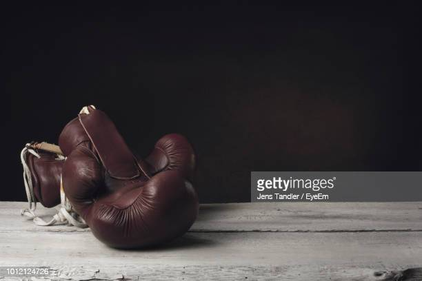 close-up of boxing gloves on table against black background - 格闘技 ストックフォトと画像