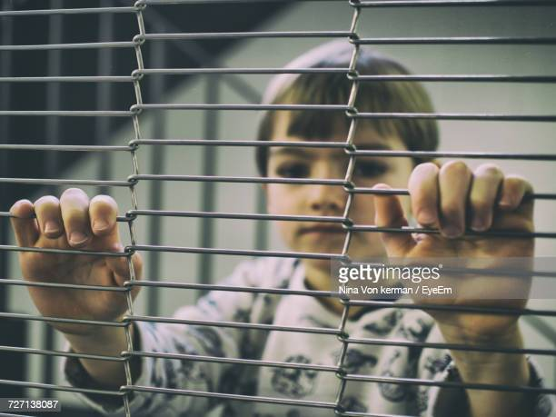 Close-Up Of Boy Behind Fence