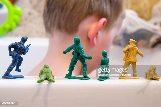 close-up of boy by toy soldiers on bathtub - army soldier toy stock pictures, royalty-free photos & images