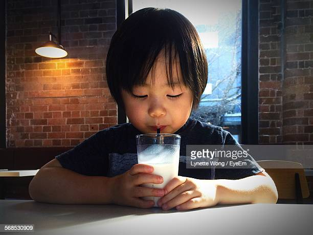 Close-Up Of Boy Drinking Milk At Dining Table Against Wall