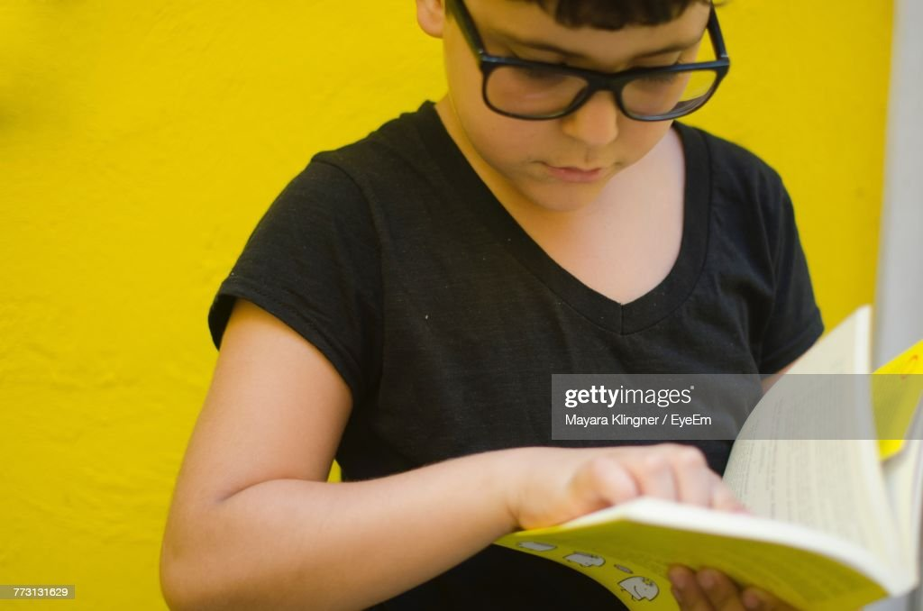 Close-Up Of Boy Holding Book : Photo